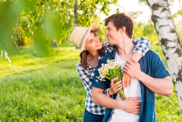 Donna con i fiori indietro che abbraccia uomo bello Foto Gratuite