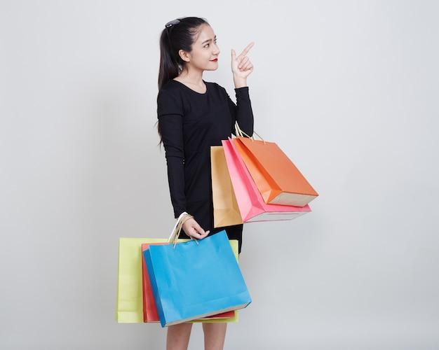 Donna con i sacchetti della spesa che stanno sul bianco Foto Premium