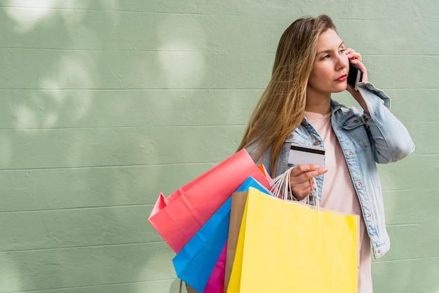 Donna con i sacchetti della spesa e carta di credito parlando per telefono Foto Gratuite