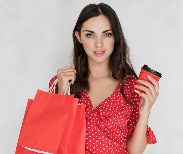 Donna con i sacchetti della spesa e il caffè rossi Foto Gratuite