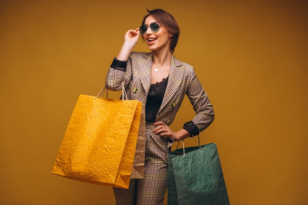 Donna con i sacchetti della spesa in studio su fondo giallo isolato Foto Gratuite