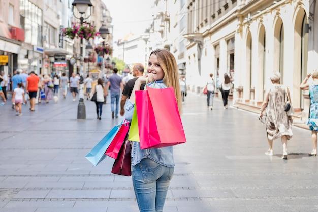 Donna con i sacchetti della spesa variopinti che esaminano macchina fotografica Foto Gratuite