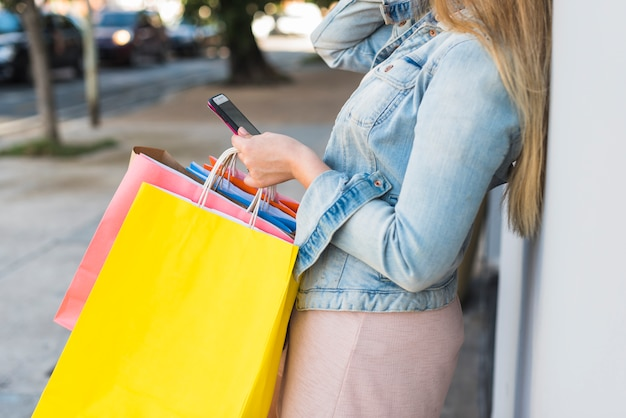 Donna con i sacchetti della spesa variopinti facendo uso dello smartphone Foto Gratuite