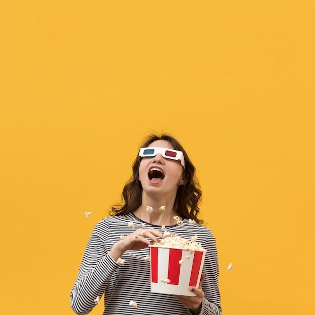 Donna con i vetri 3d che tengono un secchio con popcorn Foto Gratuite