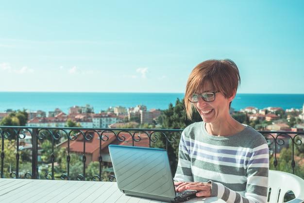 Donna con i vetri e vestiti casuali che lavorano al computer portatile all'aperto sul terrazzo Foto Premium