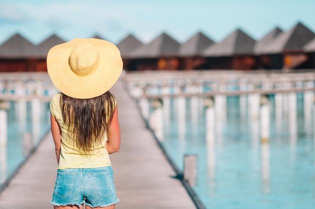 Donna con il cappello giallo che si rilassa alla piscina nella località di soggiorno esotica Foto Premium