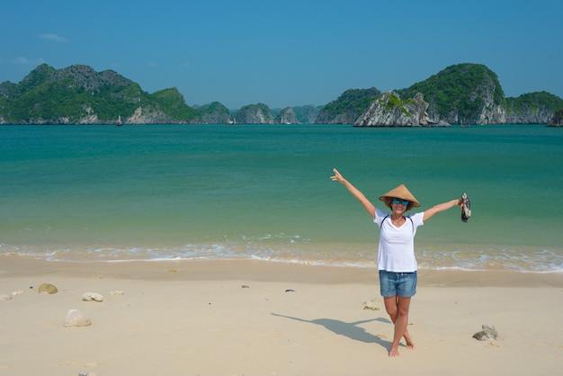 Donna con il cappello vietnamita sulla spiaggia dell'isola di cat ba halong bay, vietnam Foto Premium