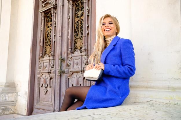 Donna con il cappotto blu sulla strada Foto Gratuite