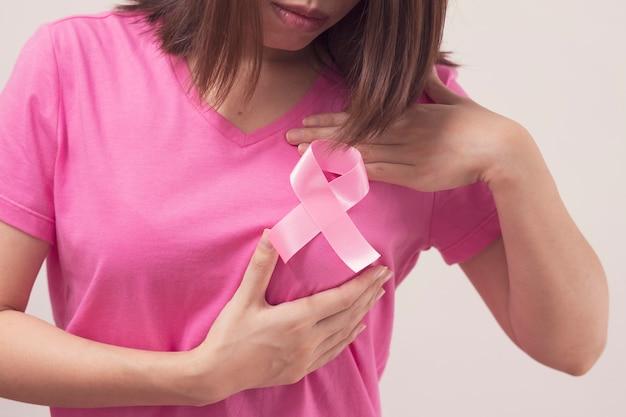 Donna con il nastro rosa che tiene il suo seno al controllo del cancro al seno. Foto Premium