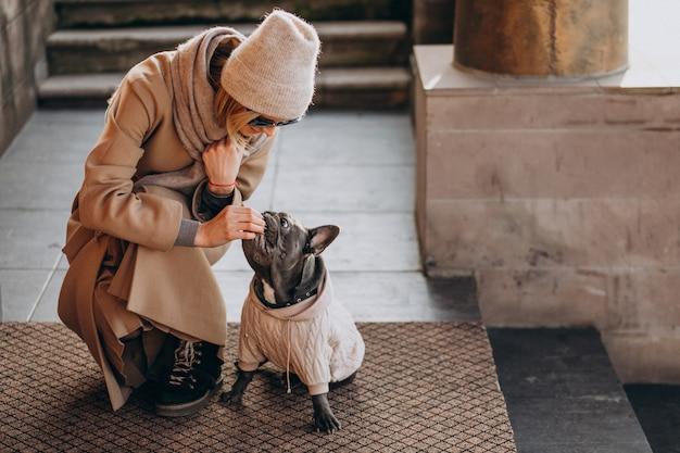 Donna con il suo bulldog francese dell'animale domestico che cammina fuori Foto Gratuite