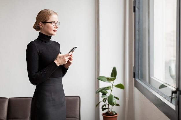 Donna con il telefono che osserva sulla finestra Foto Gratuite