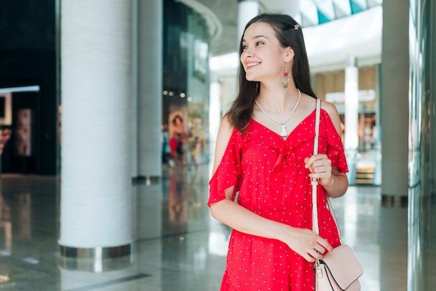 Donna con il vestito rosso che osserva via Foto Gratuite