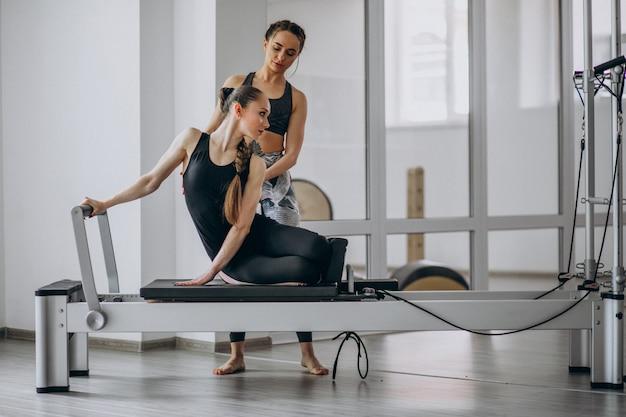 Donna con l'istruttore di pilates che si esercita nei pilates Foto Gratuite