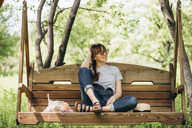 Donna con la borsa di eco con frutta in una campagna Foto Gratuite