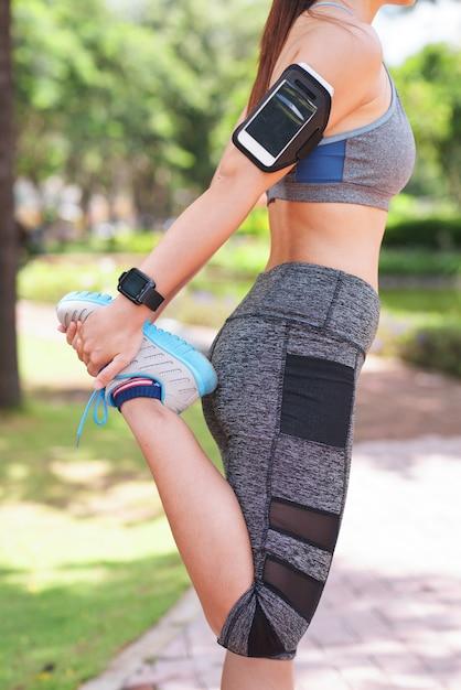 Donna con la fascia da braccio che allunga nel parco Foto Gratuite