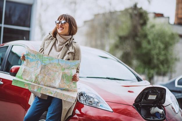 Donna con la mappa di viaggio che viaggia in auto elettrica Foto Gratuite