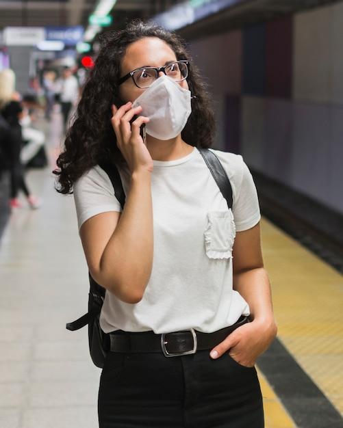 Donna con la maschera medica che parla sul telefono mentre aspettando la metropolitana Foto Gratuite
