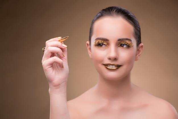 Donna con la penna d'oro nel concetto di moda Foto Premium
