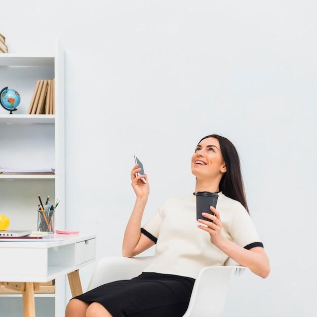 Donna con la tazza di caffè e smartphone ridendo in ufficio Foto Gratuite