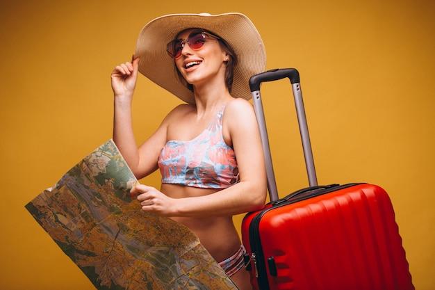 Donna con la valigia rossa e la mappa di viaggio in un vestito di nuoto isolato Foto Gratuite