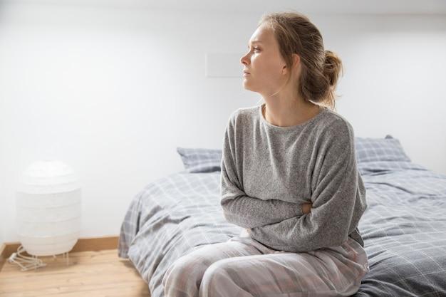 Donna con le mani sullo stomaco soffre di dolore, guardando da parte Foto Gratuite