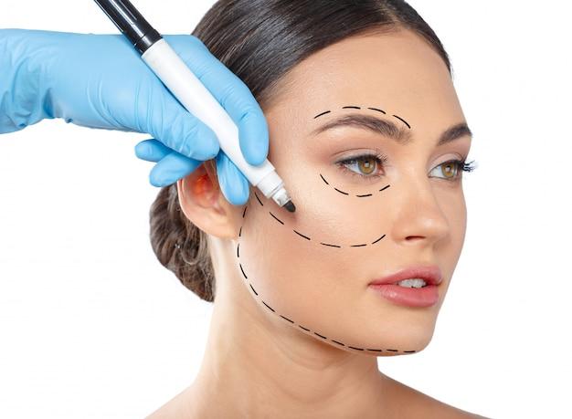 Donna con linee tratteggiate sul viso, cosmetologia Foto Premium