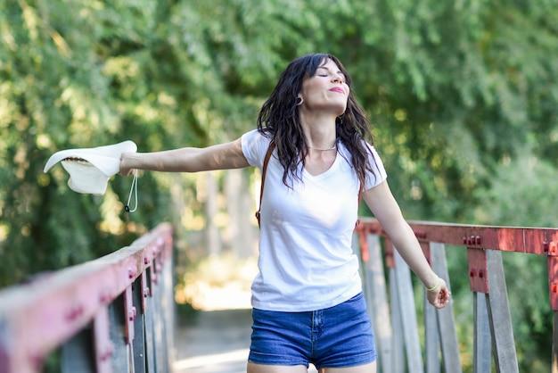 Donna con lo zaino che sta sul ponte rurale. Foto Premium