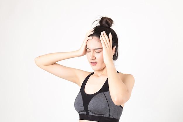 Donna con mal di testa che sente dolore. studio girato su sfondo bianco. concetto di fitness e salute Foto Premium