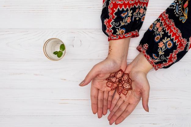 Donna con mehendi sulle palme vicino alla tazza con il ramoscello della pianta Foto Gratuite