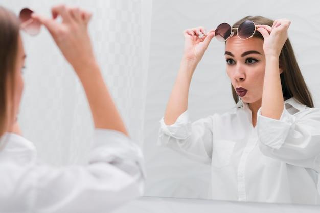 Donna con occhiali da sole guardarsi allo specchio Foto Gratuite