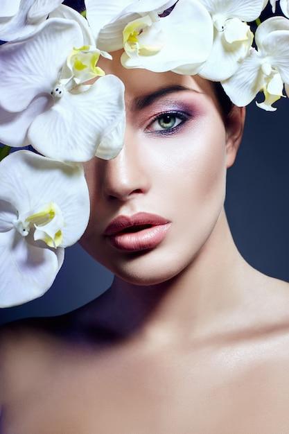 Donna con orchidea bianca vicino viso Foto Premium