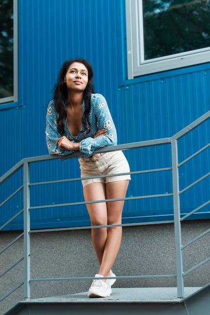 Donna con pantaloni corti guardando lontano Foto Gratuite