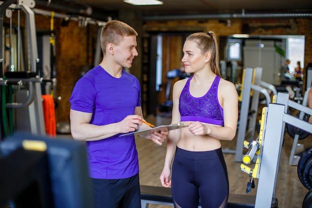 Donna con personal trainer preparando il piano di allenamento in palestra. Foto Premium