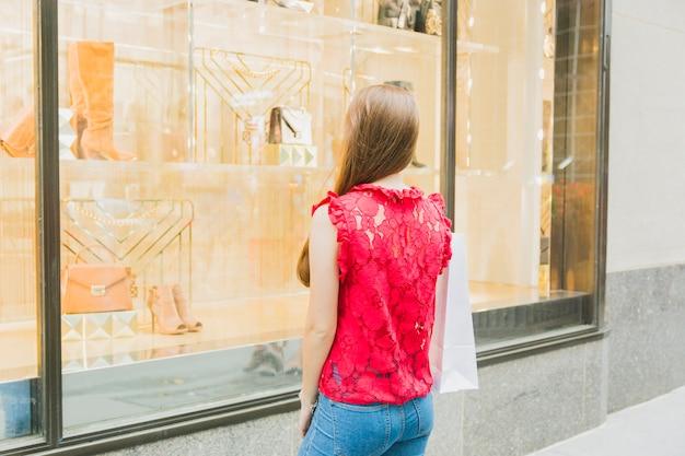 Donna con shopping indietro vicino alla finestra del negozio Foto Gratuite