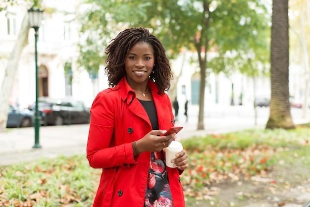 Donna con sorridere della tazza di carta e dello smartphone Foto Gratuite
