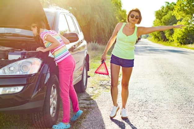 Donna con sua figlia vicino all'automobile rotta Foto Premium