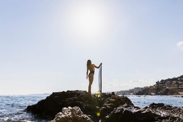 Donna con tavola da surf in spiaggia Foto Gratuite
