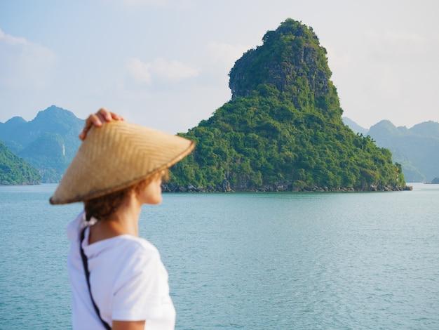 Donna con tradizionale guardando vista unica della baia di halong, vietnam. turista che viaggiano in crociera tra i pinnacoli di roccia di ha long bay nel mare. signora caucasica divertirsi in vacanza al famoso punto di riferimento. Foto Premium
