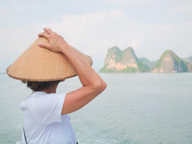 Donna con tradizionale guardando vista unica della baia di halong, vietnam. Foto Premium