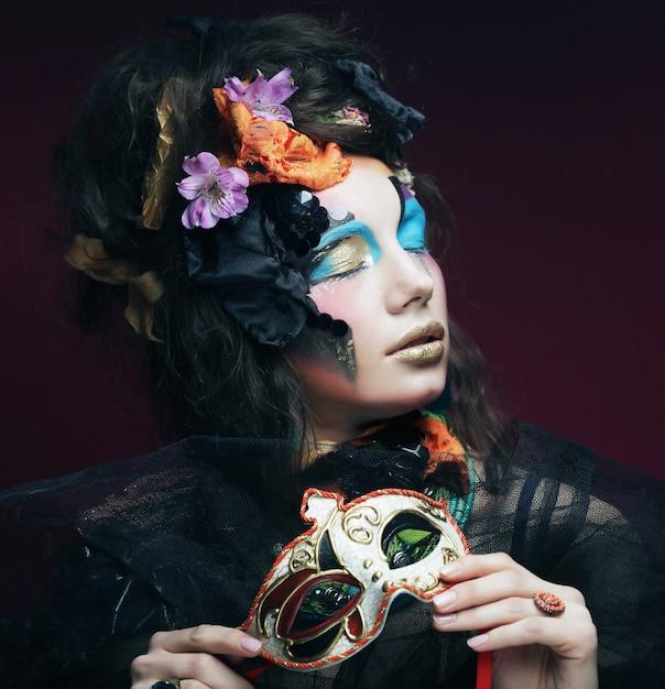 Donna con trucco luminoso con la maschera di carnevale Foto Premium