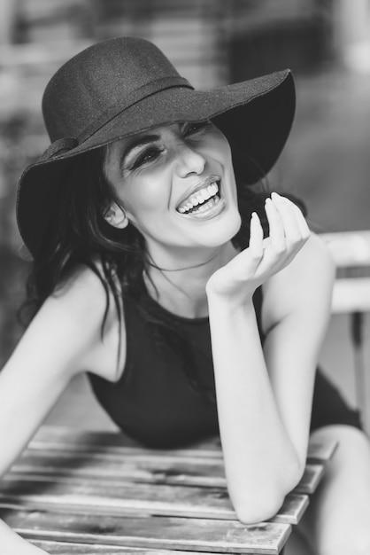 https://image.freepik.com/foto-gratuito/donna-con-un-cappello-nero-che-ride_1139-560.jpg