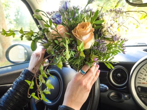 Donna con un mazzo di fiori alla guida di un'auto. Foto Premium