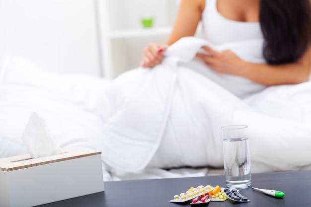Donna con un raffreddore sul letto sotto la coperta Foto Premium