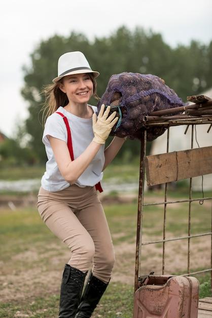Donna con un sacchetto di frutta in una fattoria Foto Gratuite