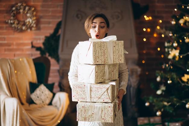 Donna con un sacco di regali davanti all'albero di natale Foto Gratuite