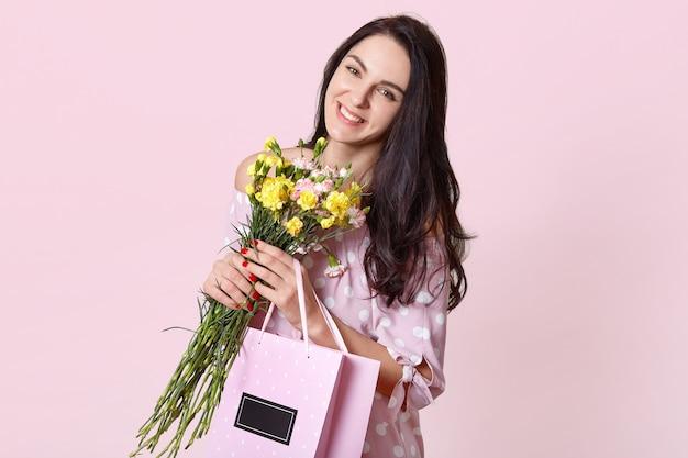 Donna con un sorriso a trentadue denti, ha lunghi capelli lisci scuri, inclina la testa, porta un mazzo di fiori e una borsa con il presente, posa sul rosa, esprime emozioni positive, ha una buona giornata Foto Gratuite