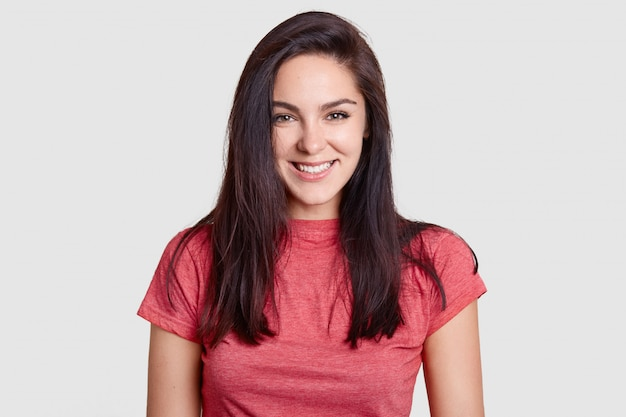Donna con un sorriso piacevole, capelli scuri, vestita con una maglietta rosa casual, ha i denti bianchi perfetti, si rallegra di ricevere complimenti Foto Gratuite