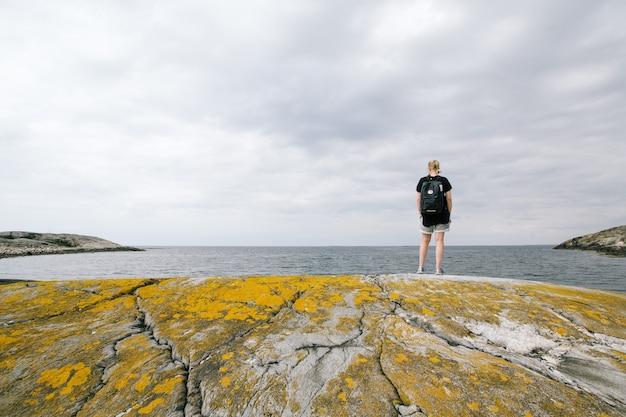 Donna con uno zaino che sta su una roccia vicino al mare con un cielo nuvoloso Foto Gratuite