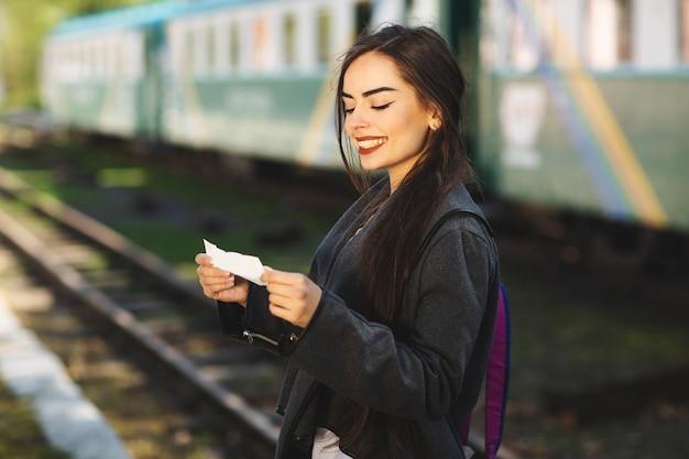 Donna con uno zaino, vicino al treno controlla il suo biglietto per la piattaforma della stazione Foto Premium