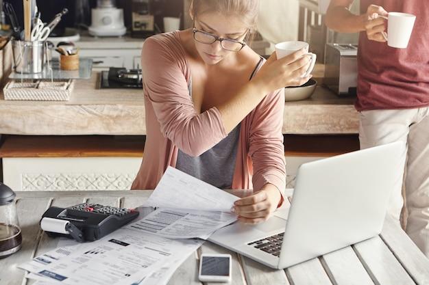 Donna concentrata vestita casualmente calcolando le bollette, seduto al tavolo della cucina con laptop, calcolatrice, documenti e cellulare, tenendo la tazza bianca e passandola a suo marito Foto Gratuite